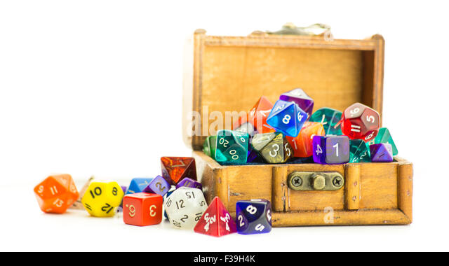A small wooden chest overflows with multicolored dice - Stock Image