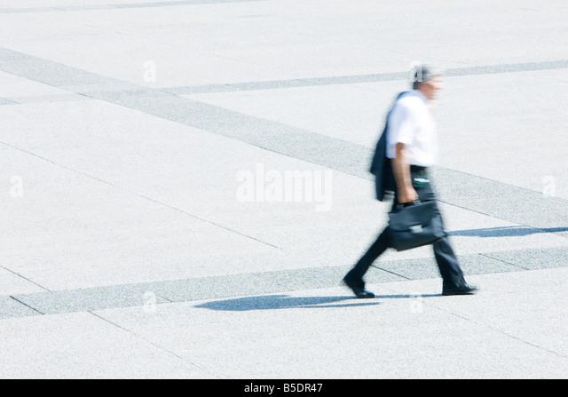 Businessman with jacket on shoulder walking across public square - Stock Image