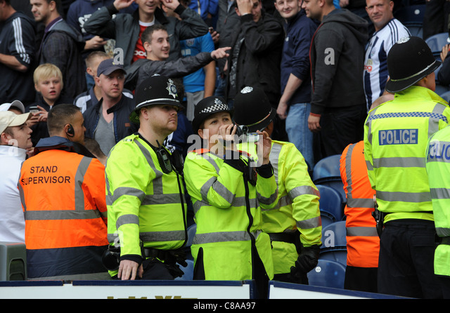 West Midlands Police officers videoing football crowd at football match Uk - Stock Image