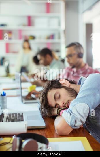 Man sleeping at desk in office - Stock-Bilder