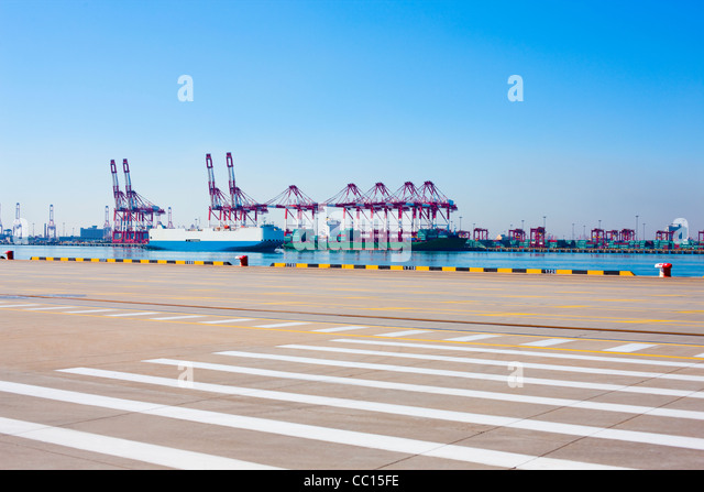 Cranes and cargo ships on the shipping dock - Stock Image