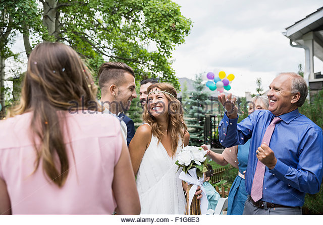 Wedding guests throwing confetti over bride and groom - Stock Image