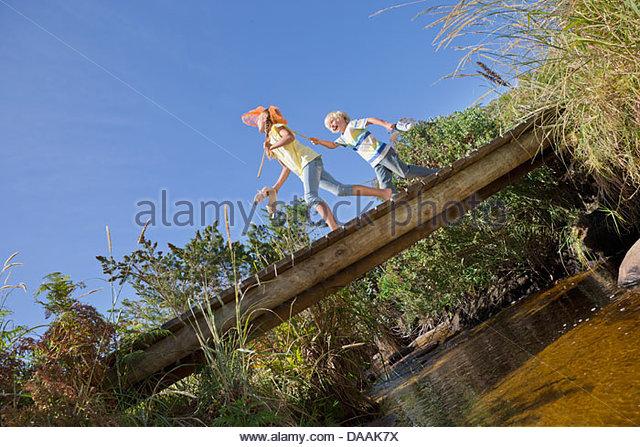 Happy boy and girl with fishing nets walking on footbridge over stream - Stock Image