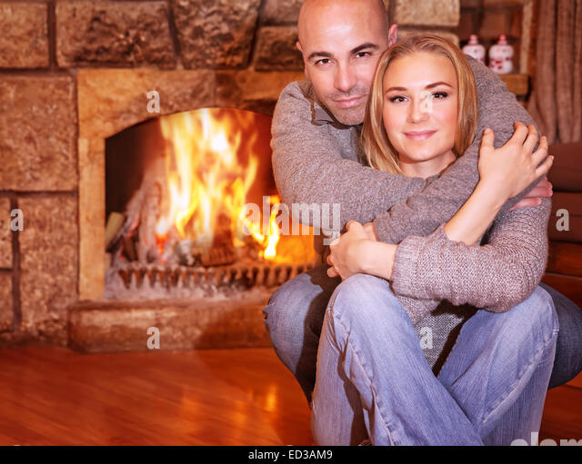 Portrait of gentle couple sitting near fireplace at home, romantic celebration of Christmas holidays, love and togetherness - Stock-Bilder