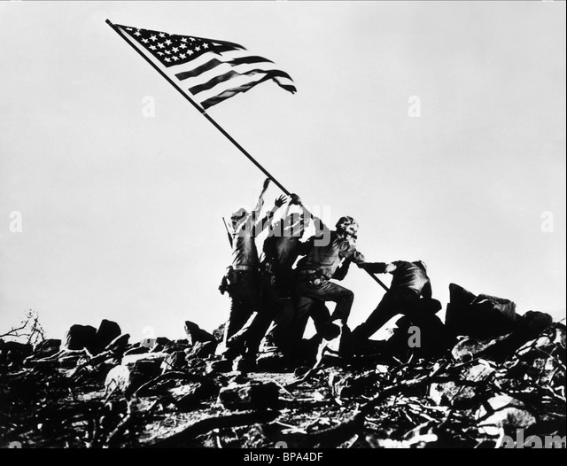 SCENE WITH TROOPS RAISING FLAG SANDS OF IWO JIMA (1949) - Stock Image
