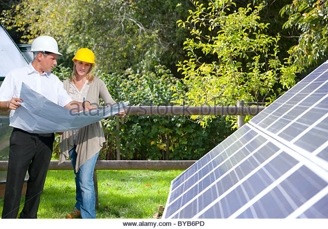 Technicians holding blueprints talking near large solar panels - Stock Image