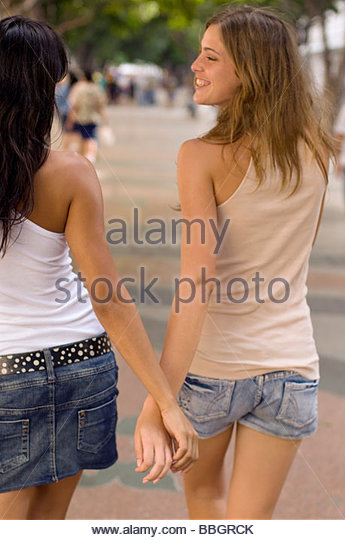 Two young woman walking on road, rear view, Havana, Cuba - Stock Image