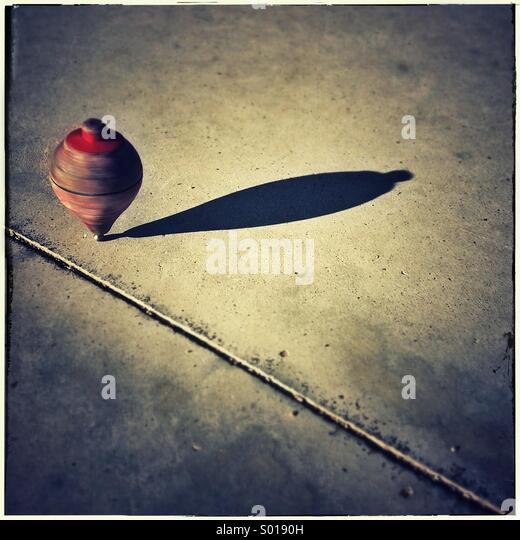 Wooden whirligig arriving into target. Old spinning top turning - Stock Image
