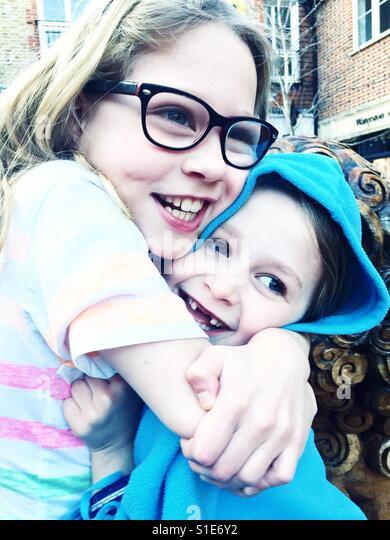 Sisters cuddling - Stock-Bilder