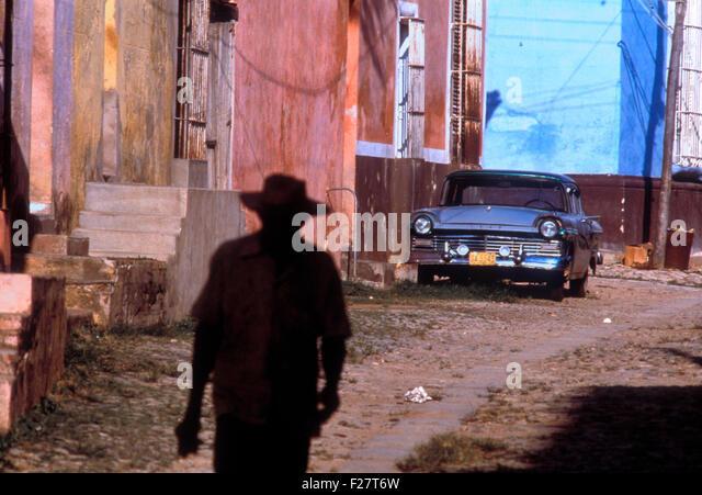 A Cuban man walks through an alley past an old Ford in Havana, Cuba. - Stock Image