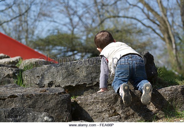 Rear View Of Boy On Rocks - Stock Image