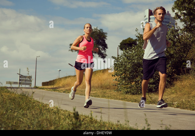 Young couple jogging down urban path - Stock Image