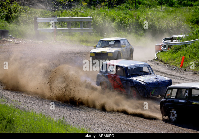 Throwing up dust and gravel Folkrace banger racing cars curve through winding country lanes at Torslanda Racecourse - Stock Image