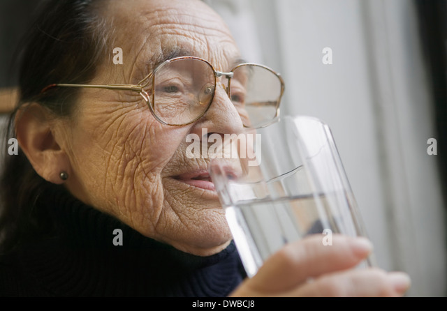 Senior woman with glass of drinking water - Stock Image