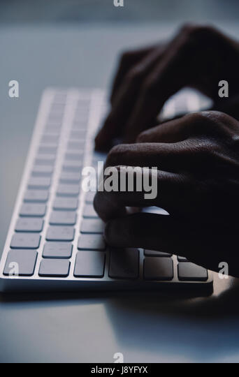 closeup of a young man typing in a computer keyboard in gloom, with a dramatic effect - Stock Image