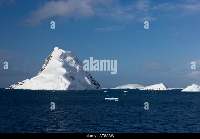 Snow capped islands of the Antarctic peninsula surrounded by icebergs and sea against a blue sky background - Stock Image
