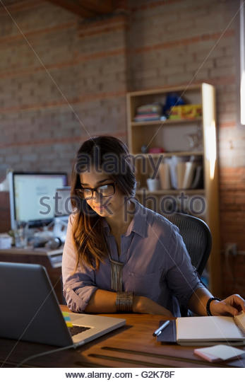 Female designer working at laptop in office - Stock Image