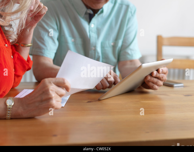 Older couple reading mail in kitchen - Stock Image