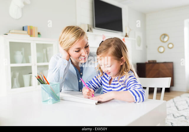 Girl (4-5) drawing with her mom - Stock-Bilder
