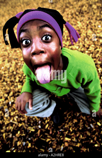 Negro boy age 8-10 pulling tongues into camera.The Image was shot from slightly above. - Stock Image