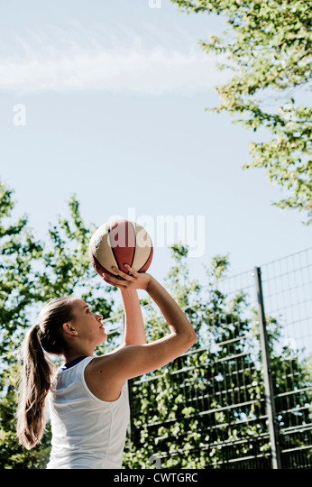 Teenage girl throwing basketball - Stock Image