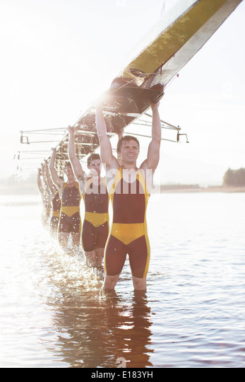 Rowing team carrying scull overhead in lake - Stock Image