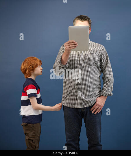 adult ignoring child while looking at tablet - Stock Image