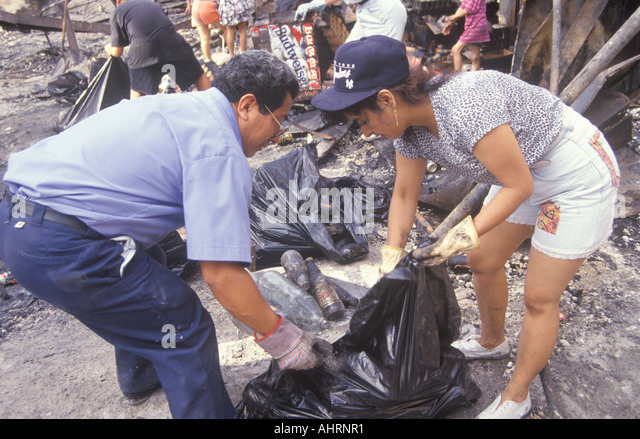 Couple cleaning up after 1992 riots South Central Los Angeles California - Stock Image