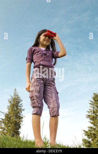 Young elementary age school girl, 8 years old, playing outside enjoying childhood. - Stock Image