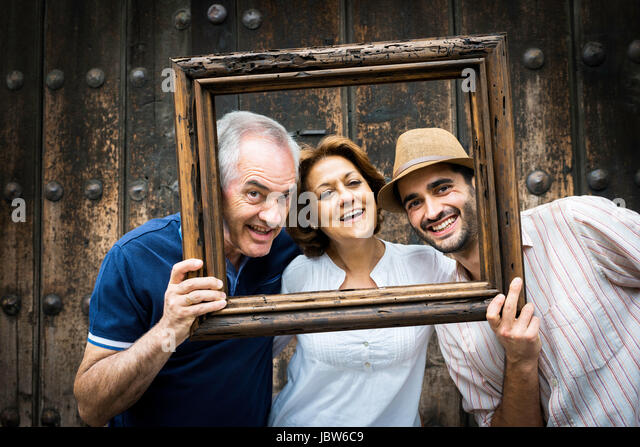 Portrait of adult family, holding wooden frame in front of their faces, Mexico City, Mexico - Stock-Bilder