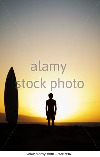 man with surfboard watching sunset at the beach - Stock Image