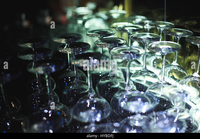 Inverted empty glasses arranged in several rows. The focus in the center of the frame - Stock Image