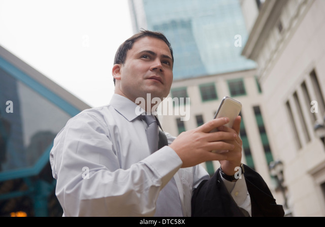 Businessman in city surrounded by skyscrapers - Stock-Bilder