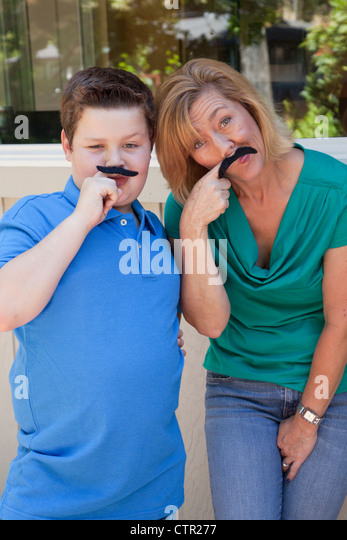 Mom and son are playing with fake mustaches. - Stock Image