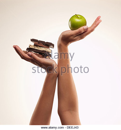Woman cupping green apple above chocolate bars - Stock Image