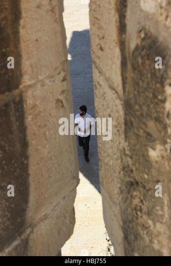 A Jewish man is seen through a gap in the Walls of Jerusalem in 2016. - Stock-Bilder