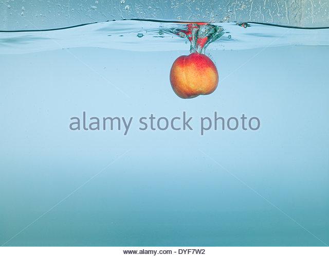 Apple splashing in water - Stock Image