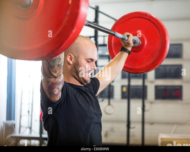 Athlete Exercising With Barbell At Gym - Stock-Bilder
