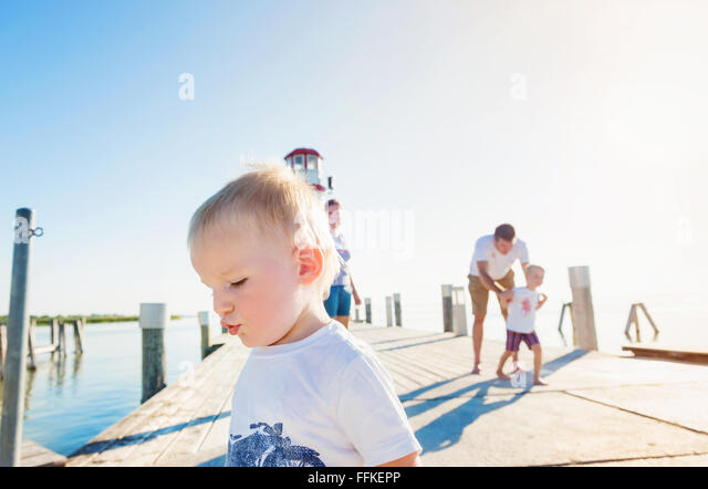 Family on the pier at the lighthouse, sunny summer - Stock-Bilder