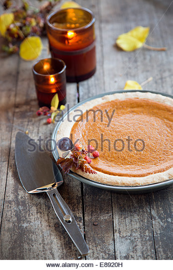 Pumpkin pie and candles on rustic wood table - Stock Image