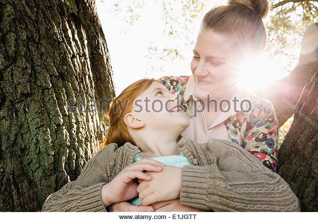 Portrait of mid adult mother and daughter in park - Stock Image