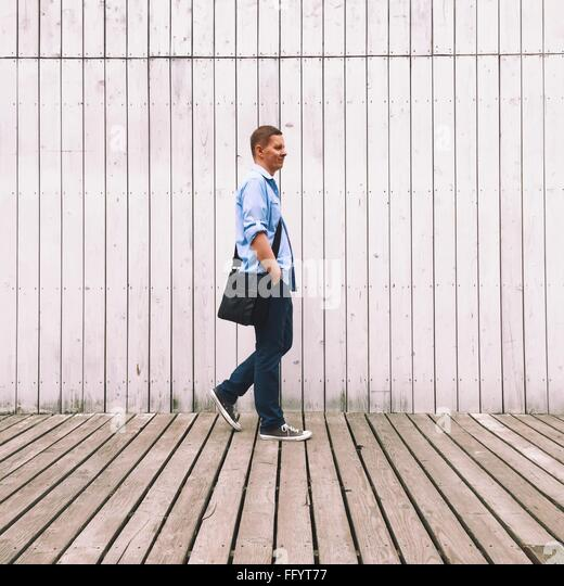 Side View Of Man Walking Against Wall - Stock Image