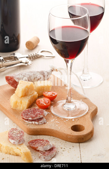 Two wineglasses with red wine and assortment of cheese and fruits on white background - Stock-Bilder