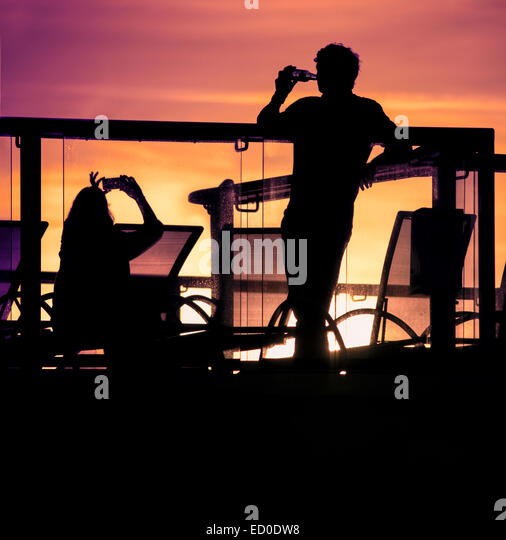 England, Southampton, Silhouettes of couple relaxing on balcony at sunset - Stock-Bilder