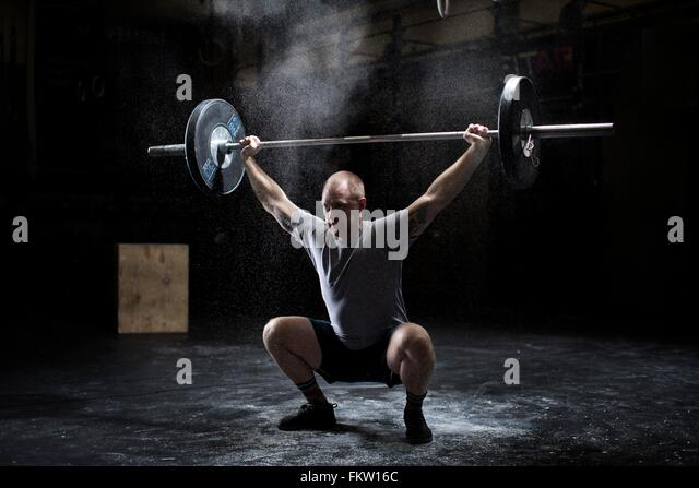 Young man weightlifting barbell in dark gym - Stock Image