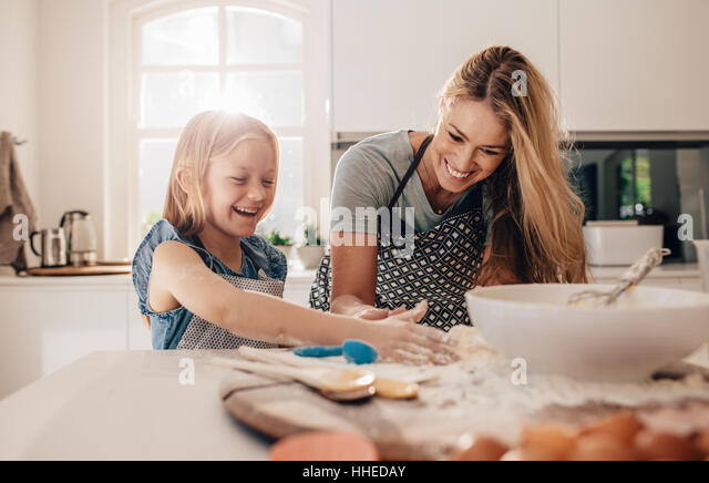 Happy young girl with her mother making dough. Mother and daughter baking in kitchen. - Stock Image