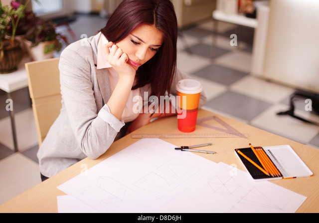 Pensive young architect having a problem with her technical drawings - Stock-Bilder