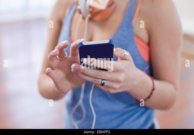 Cropped shot of teenage girl using smartphone touchscreen in ballet school - Stock Image