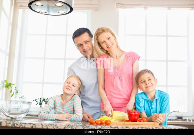 Portrait of happy family preparing food in kitchen - Stock Image