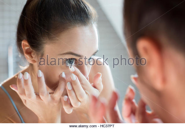 Mid adult woman applying contact lens in bathroom mirror. - Stock Image